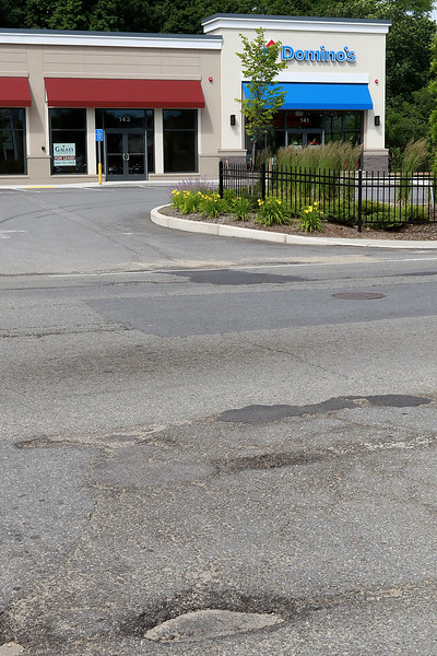 A pothole in front of Domino's on Water Street in Fitchburg on Wednesday morning, June 20, 2018. SENTINEL & ENTERPRISE/JOHN LOVE