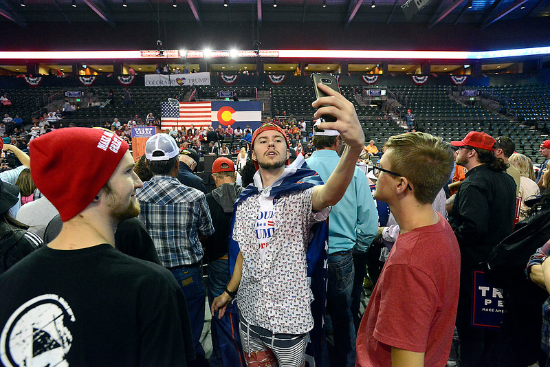 Wearing a Trump flag as a cape, Austin Marshall takes a selfie Monday, Oct. 3, 2016, during a Donald Trump rally at the Budweiser Events Center in Loveland. (Photo by Jenny Sparks/Loveland Reporter-Herald)