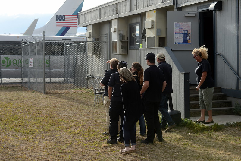 People hoping to catch a glimpse of Donald Trump descending the steps of his plane Monday, Oct. 3, 2016, at the Northern Colorado Regional Airport in Loveland gather at a vantage point with a slim view of the jet between buses and trucks parked along the airport fence. (Photo by Craig Young / Loveland Reporter-Herald)