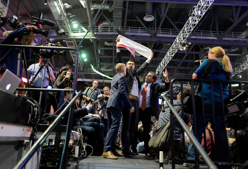 A protester is escorted off the media riser Monday, Oct. 3, 2016, during a Donald Trump rally at the Budweiser Events Center in Loveland. (Photo by Jenny Sparks/Loveland Reporter-Herald)