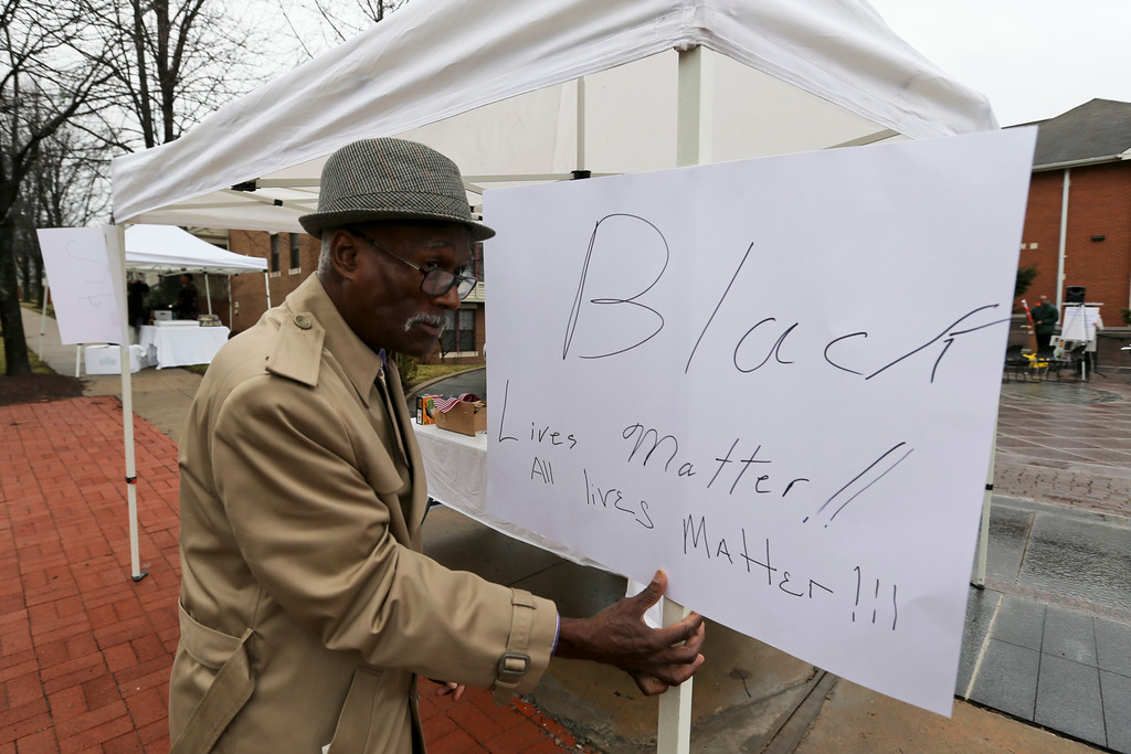 """. Jerry McKeithen puts up a sign as he works with a group to prepare the area at Freedom Corner where people are planning to hold a \""""Peoples Inauguration\"""" on Friday, Jan. 20, 2017, in Pittsburgh. (AP Photo/Keith Srakocic)"""