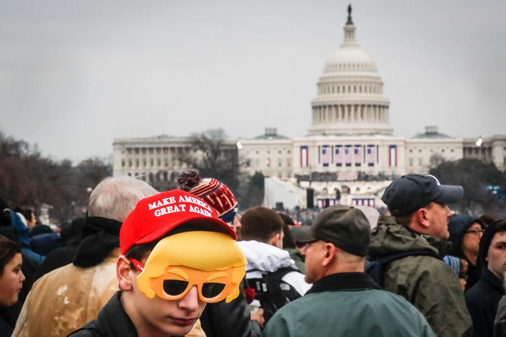 . Spectators wait in the rain on the National Mall in Washington, Friday, Jan. 20, 2017, before the presidential inauguration of Donald Trump. (AP Photo/John Minchillo)