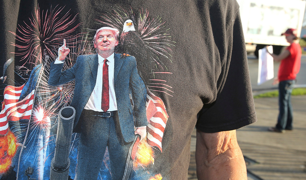 . Donald Trump supporter Glen Leirer wears a Trump t-shirt as he waves at passing motorists in Panama City, Fla.,  on Friday, January 20, 2017.   Trump will be sworn in Friday as the 45th president of the United States.  (Andrew Wardlow /News Herald via AP)