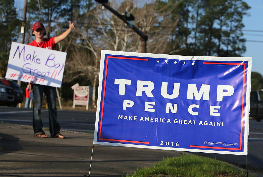 . Donald Trump supporter Jessi Johnson waves at passing motorists in Panama City, Fla.,  on Friday, January 20, 2017.   Trump will be sworn in Friday as the 45th president of the United States.  (Andrew Wardlow /News Herald via AP)