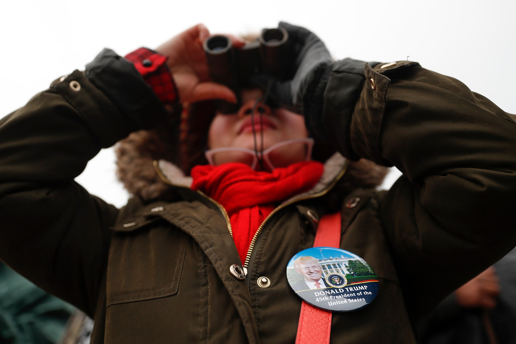 . A spectator uses binoculars to look out onto the Capitol Building before the inauguration of President-elect Donald Trump, Friday, Jan. 20, 2017, in Washington. (AP Photo/John Minchillo)