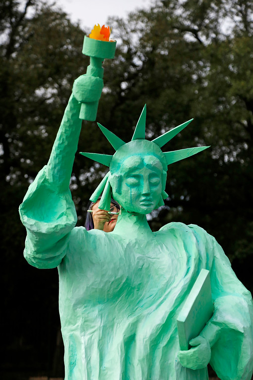 . Artist Chandra Leming paints a Statue of Liberty sculpture she created for a protest against the inauguration of Donald Trump at Louis Armstrong Park in New Orleans, Friday, Jan. 20, 2017. Donald J. Trump will be sworn in as the 45th President of the United States Friday. (AP Photo/Max Becherer)