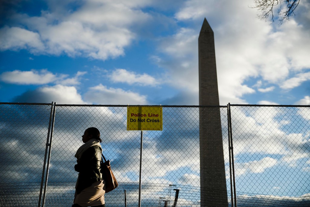 . A woman passes a barricade in view of the Washington Monument as preparations continue for Friday\'s inauguration of Donald Trump in Washington, Wednesday, Jan. 18, 2017. (AP Photo/Matt Rourke)