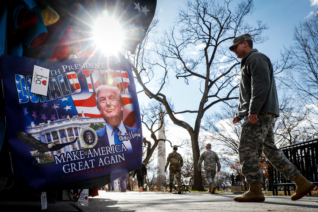 . Military personnel walk along the National Mall in Washington, Wednesday, Jan. 18, 2017, alongside vendors selling President-elect Donald Trump merchandise ahead of Friday\'s presidential inauguration. (AP Photo/John Minchillo)