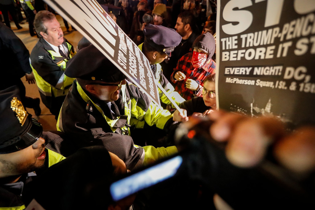 . Police push protesters off the sidewalk in front of the National Press Building ahead of the presidential inauguration, Thursday, Jan. 19, 2017, in Washington. (AP Photo/John Minchillo)