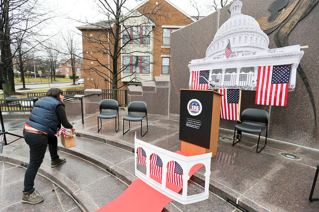 """. Suzy South prepares the area at Freedom Corner where people are planning to hold a \""""Peoples Inauguration\"""" on Friday, Jan. 20, 2017, in Pittsburgh. (AP Photo/Keith Srakocic)"""