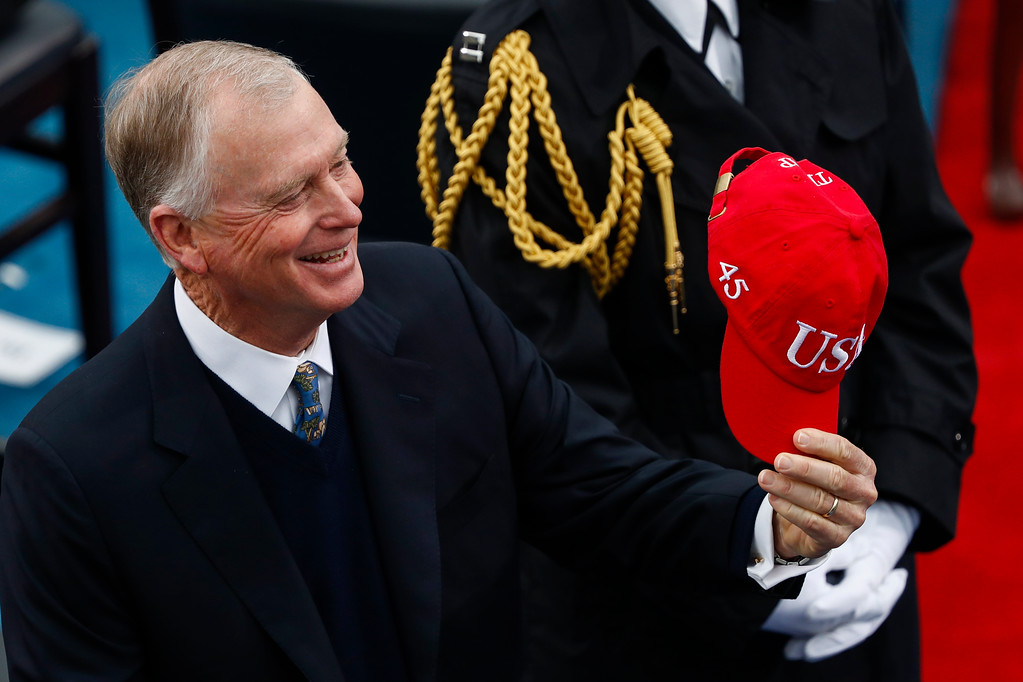 . Former Vice President Dan Quayle holds up a red Trump ball cap during the 58th Presidential Inauguration at the U.S. Capitol in Washington, Friday, Jan. 20, 2017. (AP Photo/Carolyn Kaster)