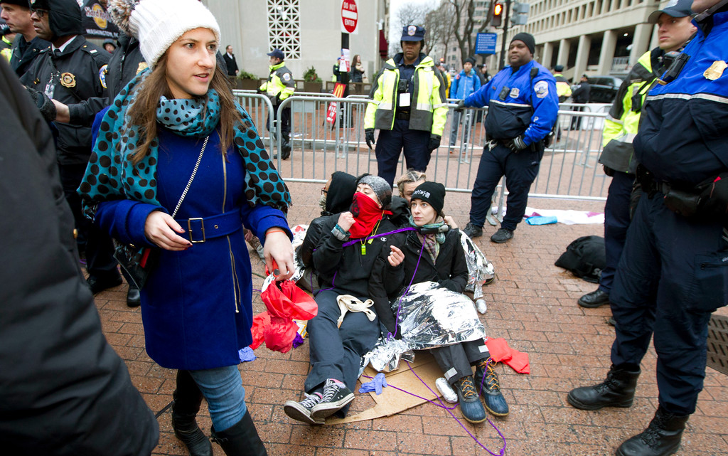 . Demonstrators sit on a sidewalk attempting to block people entering a security checkpoint, Friday, Jan. 20, 2017, ahead of President-elect Donald Trump\'s inauguration in Washington. ( AP Photo/Jose Luis Magana)
