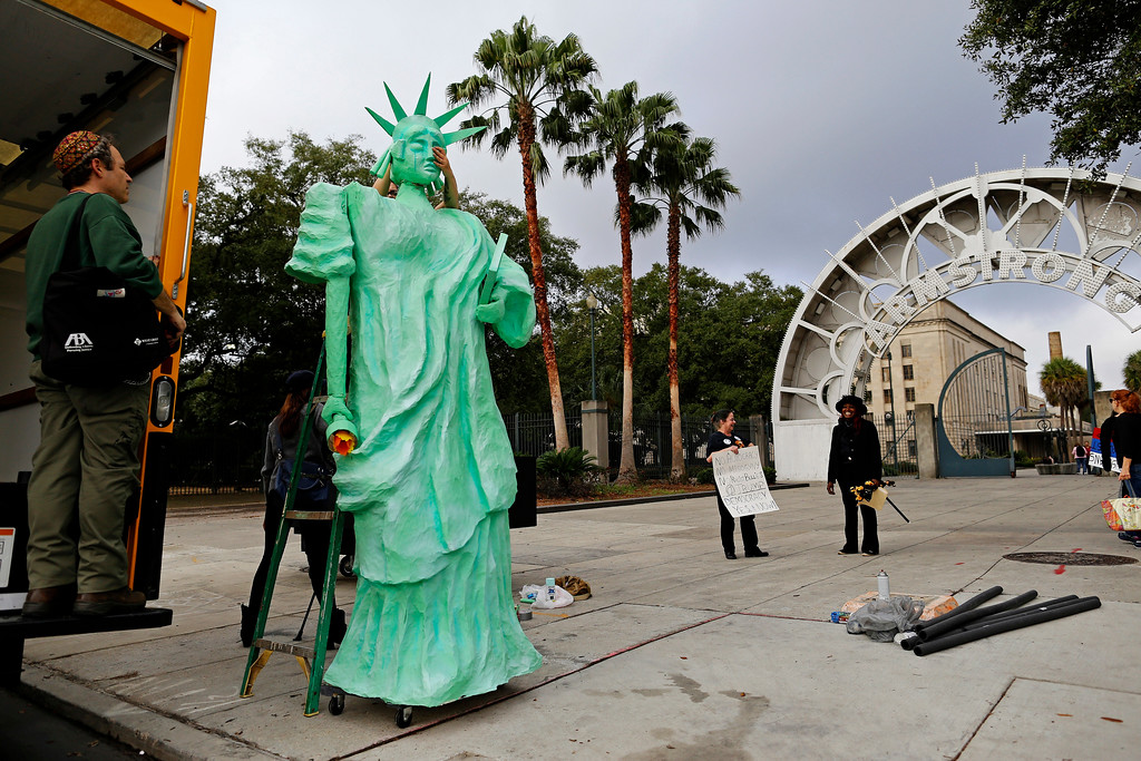 . Artist Chandra Leming places the head on a Statue of Liberty sculpture she created for a protest against the inauguration of Donald Trump at Louis Armstrong Park in New Orleans, Friday, Jan. 20, 2017. Donald Trump will be sworn in as the 45th President of the United States Friday. (AP Photo/Max Becherer)