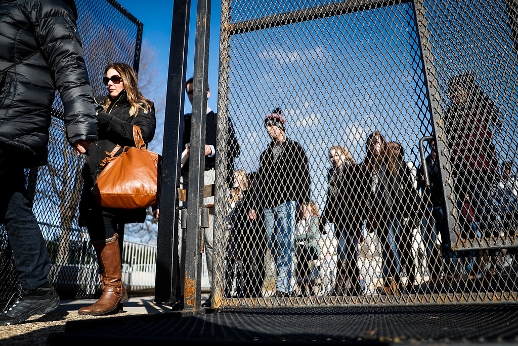 . Pedestrians pass through tall security fencing erected around the National Mall in Washington, Wednesday, Jan. 18, 2017, as preparations continue for Friday\'s presidential inauguration. (AP Photo/John Minchillo)