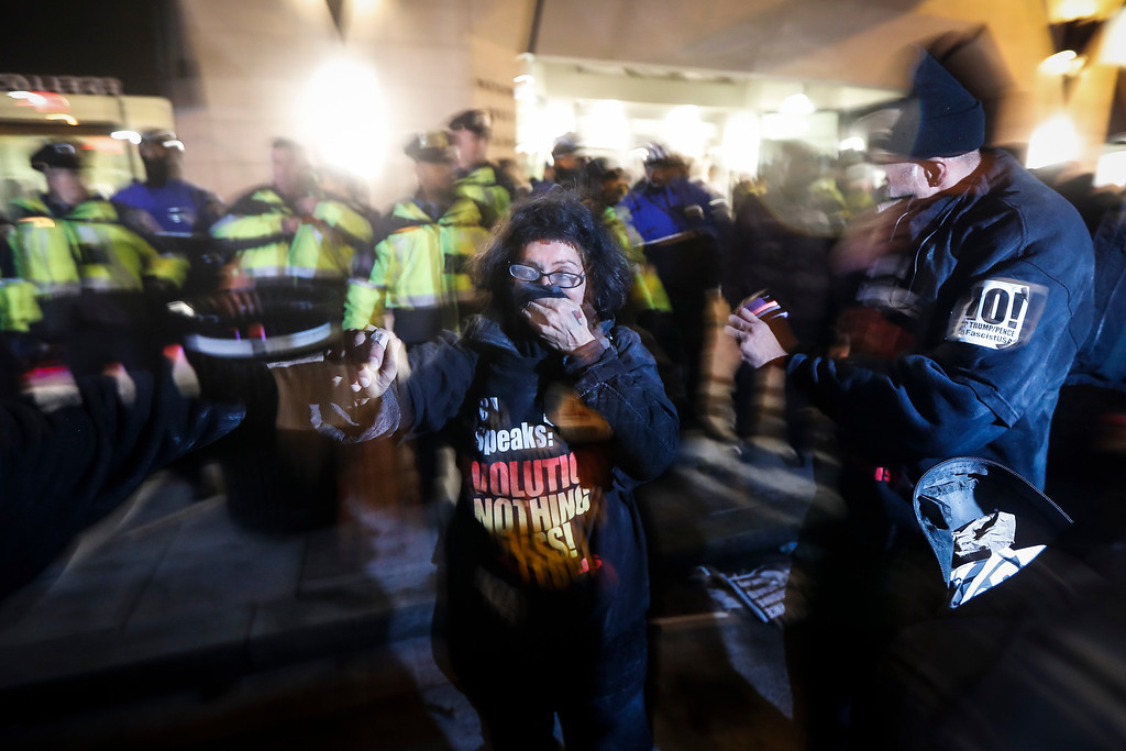 . Protesters cover their faces after being pepper sprayed following a scuffle outside the National Press Club ahead of the presidential inauguration, Thursday, Jan. 19, 2017, in Washington. (AP Photo/John Minchillo)