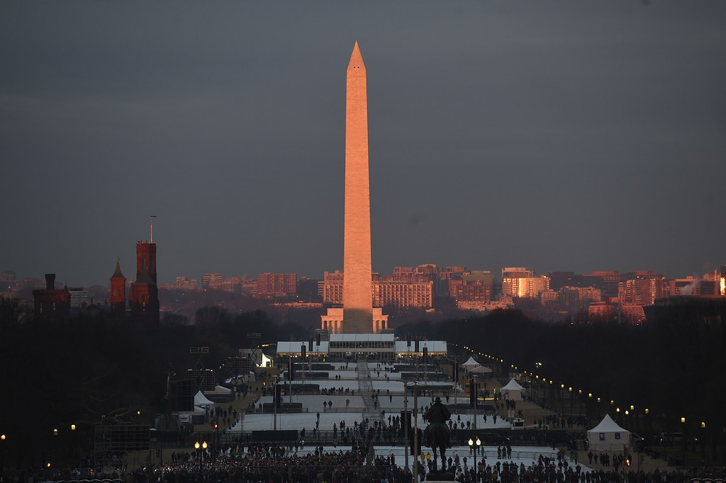 . People gather on the National Mall, looking from Capitol Hill to the Washington Monument and Lincoln Memorial, in Washington, Friday, Jan. 20, 2017, before the presidential inauguration of Donald Trump.  (Saul Loeb via AP, Pool)