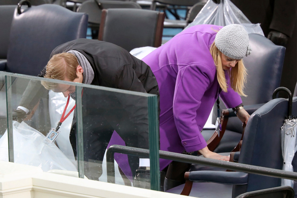 . Capitol Hill staff members wipe off the seats on the podium before the swearing in of Donald Trump as the 45th president of the United States during the 58th Presidential Inauguration at the U.S. Capitol in Washington, Friday, Jan. 20, 2017. (AP Photo/Andrew Harnik)