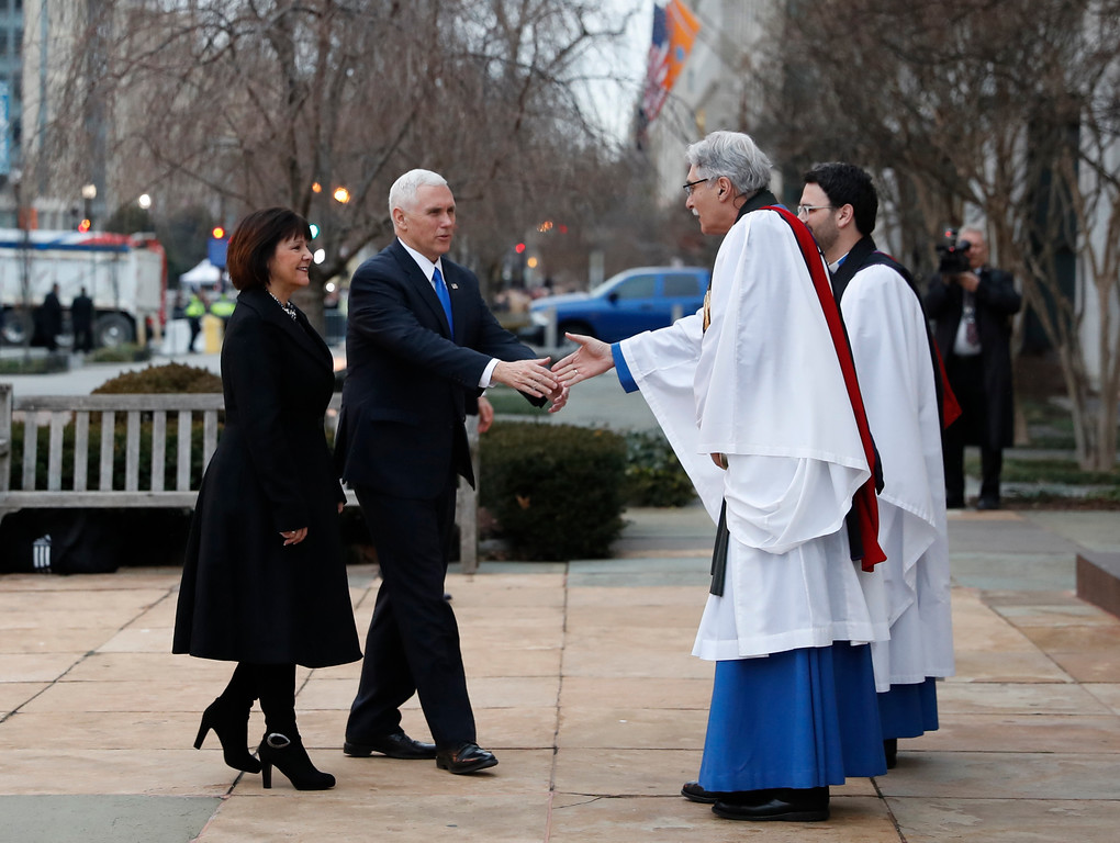 . Rev. Luis Leon greets Vice President-elect Mike Pence and his wife Karen as they arrive for a church service at St. John�s Episcopal Church across from the White House in Washington, Friday, Jan. 20, 2017, on Donald Trump\'s inauguration day. (AP Photo/Alex Brandon)