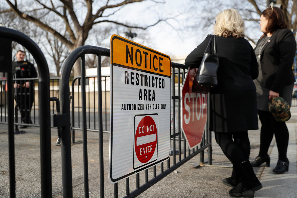 . Pedestrians pause at a guarded security checkpoint along 15th Street in Washington, Thursday, Jan. 19, 2107, as security tightens ahead of Friday\'s presidential inauguration. (AP Photo/John Minchillo)