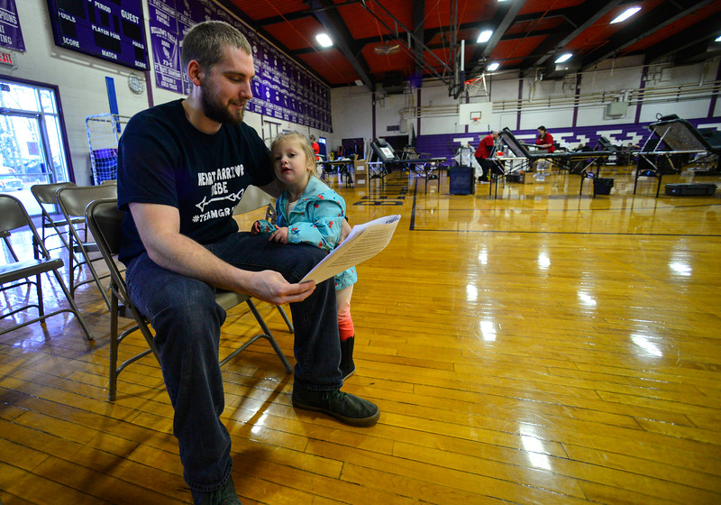 KRISTOPHER RADDER — BRATTLEBORO REFORMER<br /> Kyle O'Rourke reads the paperwork to donate blood as his daughter, Aubree, 2, gives him a hug during a blood drive in honor of Grady Oliver Evans at Bellows Falls Union High School, in Westminster, Vt., on Saturday, Feb. 29, 2020.