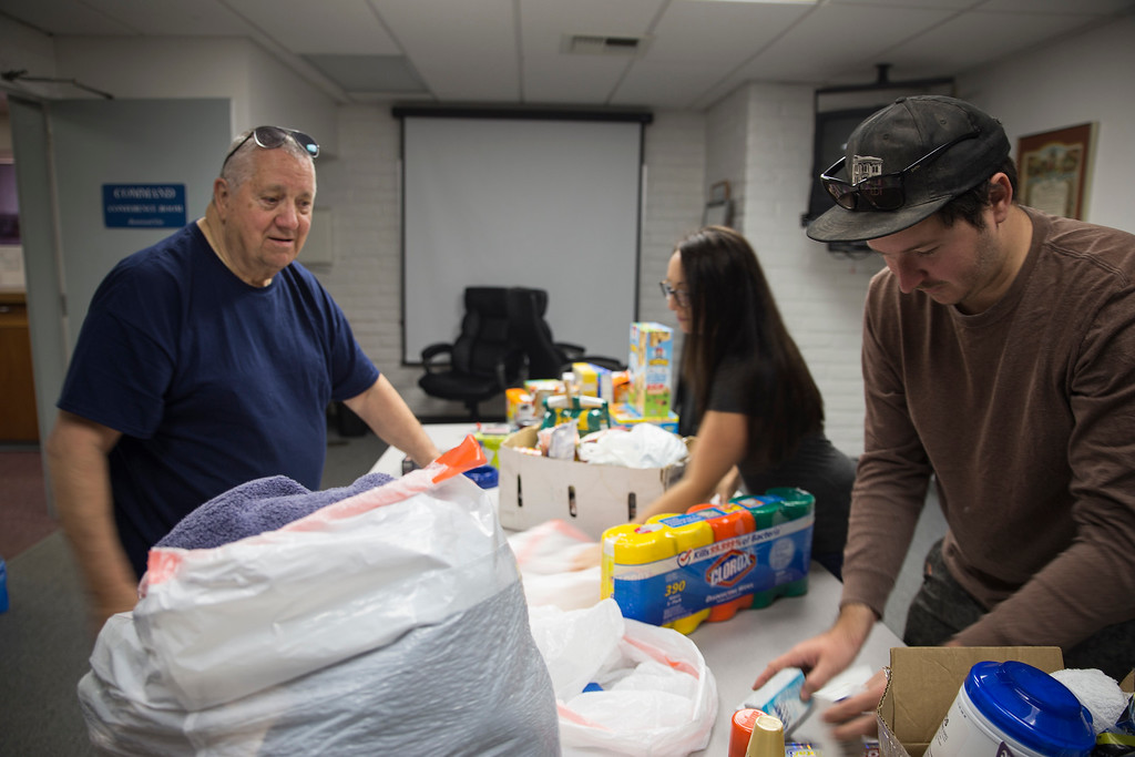 . Mervyn Dody, a Eureka resident, speaks with Austin Allison about the donations going down to help people devastated by the fires. (Sam Armanino - The Times-Standard)
