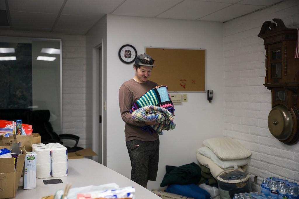 . Austin Allison looks through blankets donated for evacuees in Santa Rosa and Ukiah. (Sam Armanino - The Times-Standard)