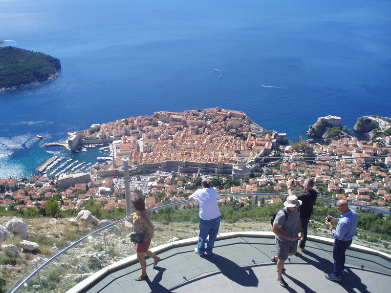 The old city of Dubrovnik is a peninsula, surrounded by high walls and fortress towers.  Inside the old city are hotels, restaurants, churches, shops and private homes.  This view is from the cable car landing above the city.