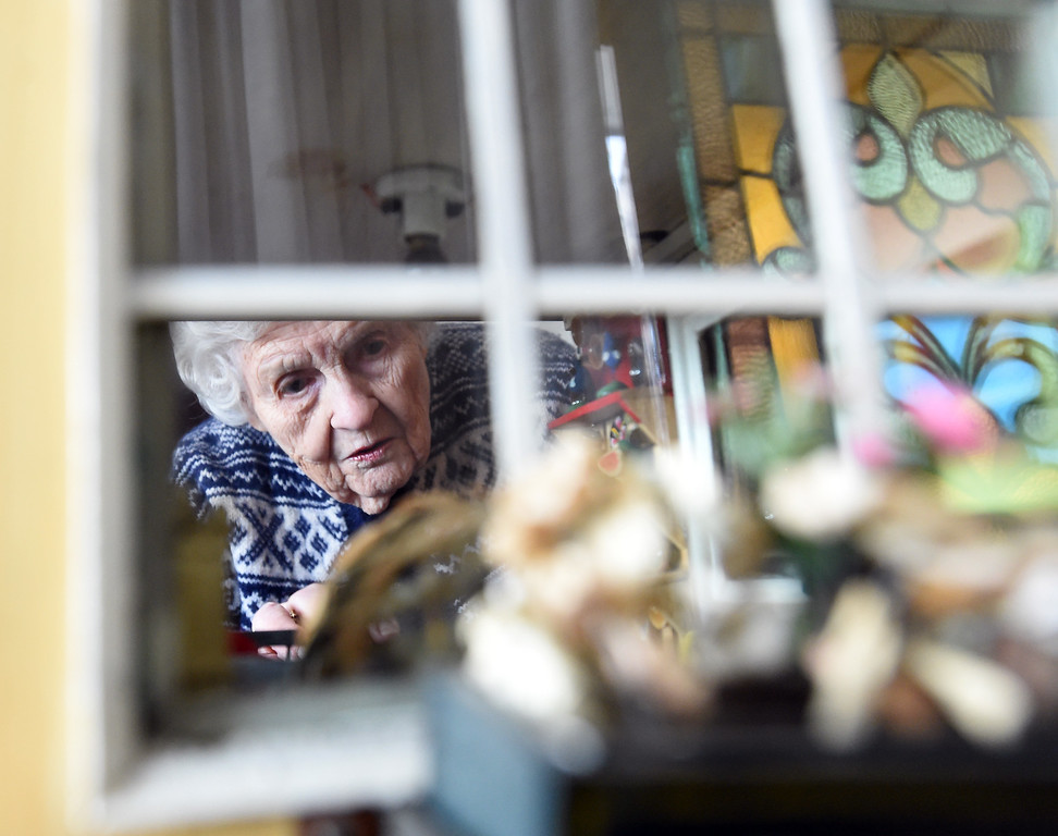 . Doris Hass, 97, of Boulder, looks through one of the windows of the dollhouse her father and paternal grandfather built for her around 1925 when the family lived on Long Island in New York.  Cliff Grassmick  Photographer January 12, 2018