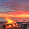 Beach fire, glass of wine, pink sky, anticosti island