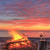 Beach fire, glass of wine, pink sky, anticosti island