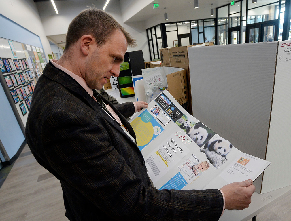 . BOULDER, CO - November 29, 2018:  Douglass Principal, Jonathan Wolfer, looks over a project at the Kids Care Expo at Douglass Elementary in Boulder.  (Photo by Cliff Grassmick/Staff Photographer)