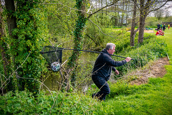 An official retrieves a wayward ball from the River Nadder that is adjacent to the home ground of Tisbury United