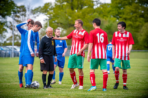 The referee shares a joke with the players of Okeford United and Portland Panthers during their Dorset League Cup tie