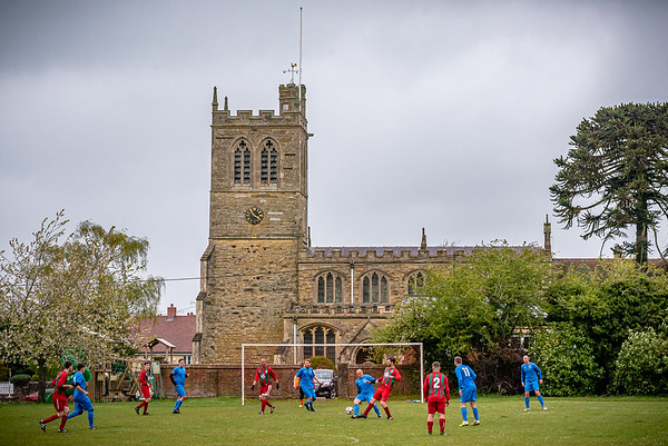 Wingrave and Quainton in action during their Aylesbury League game in front of St Peter and St Paul's Church