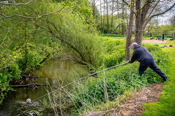 An official tries to retrieve a wayward ball from the River Nadder that is adjacent to the home ground of Tisbury United
