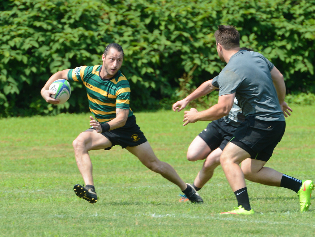 . Kevin Hockings, left, jukes away from opposing tacklers in Doylestown Rugby Club\'s third annual \'7s\' tournament. (John Gleeson � 21st-Century Media)