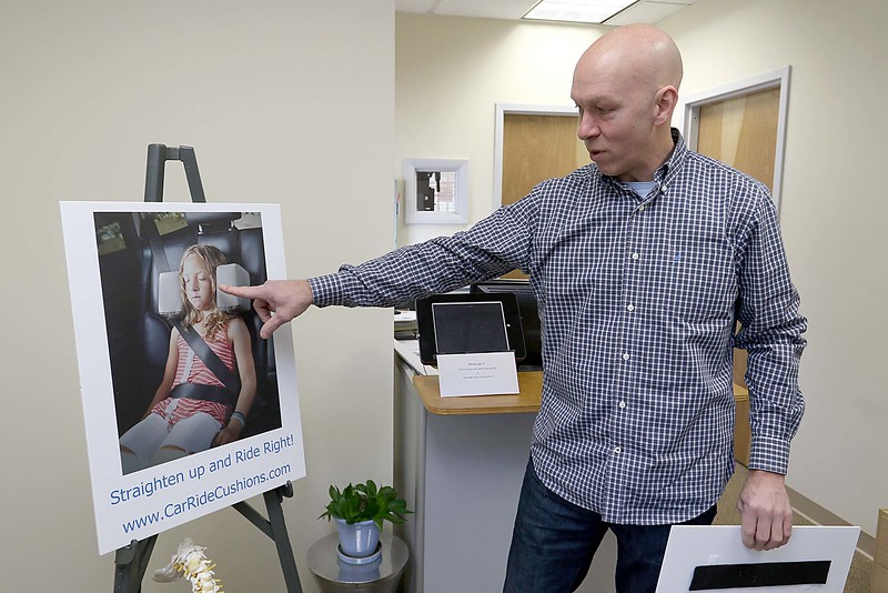 "Doctor Jim Cormier's talks about his invention the ""Car Ride cushions"" at his chiropractic office in Leominster on Thursday morning. He shows pictures of his daughter Chelsea, 7 in the pictures, with the cushions. SENTINEL & ENTERPRISE/JOHN LOVE"