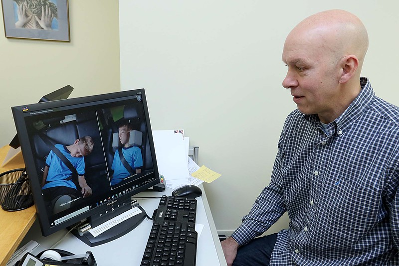 """Doctor Jim Cormier's talks about his invention the """"Car Ride cushions"""" at his chiropractic office in Leominster on Thursday morning. He shows pictures of his son Cameron, 9 in the pictures, with and without the cushions. SENTINEL & ENTERPRISE/JOHN LOVE"""