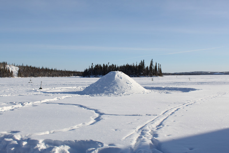 That mound of snow out on frozen Blachford Lake is a quinzhee. Unlike an igloo, which is a long-term structure made from ice blocks, a quinzhee is a temporary shelter made by digging a hollow in compacted, piled snow. The word is from the Athabaskan language.