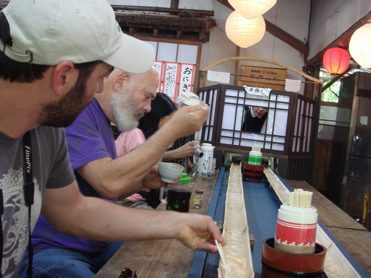 Proper technique: Fresh-plucked noodles are dipped into tsuyu sauce before eating. Delicious! (Note the noodle-maker behind the screen, checking to make sure his customers are happy.)