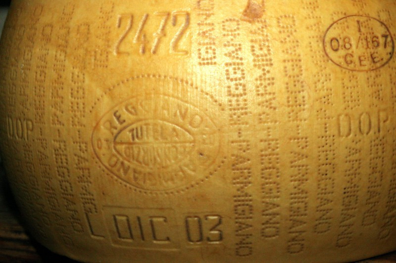 "How to read a cheese wheel. A wheel of Lucini Organics Parmigiano Reggiano, close-up. On the side of every wheel is the fire-mark stamp of the Consortium, the registration number of the production farm, and the month and year of production. On the whole rind you see the words: Parmigiano Reggiano. More importantly, you can see ""D.O.P."" and the European Economic Community stamp, identifying the production farm."