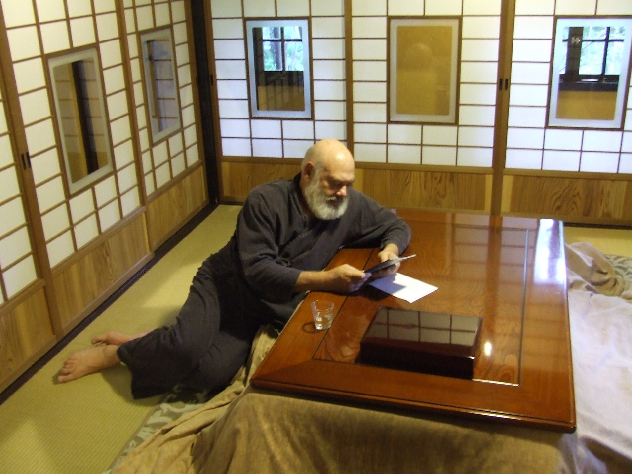 There's nothing like the serenity of a ryokan, a traditional Japanese inn. Note the kotatsu, a low wooden table covered with a futon. A heat source beneath heats the space under the table; the surrounding comforter holds in the warmth. Putting your legs under such a table is a wonderful way to keep warm efficiently. It works especially well if you are wearing a traditional samue, as I am. The heat rises through the garment's open bottom and exits the neck, keeping the whole body warm. But on this pleasant May evening, extra heat was not necessary.