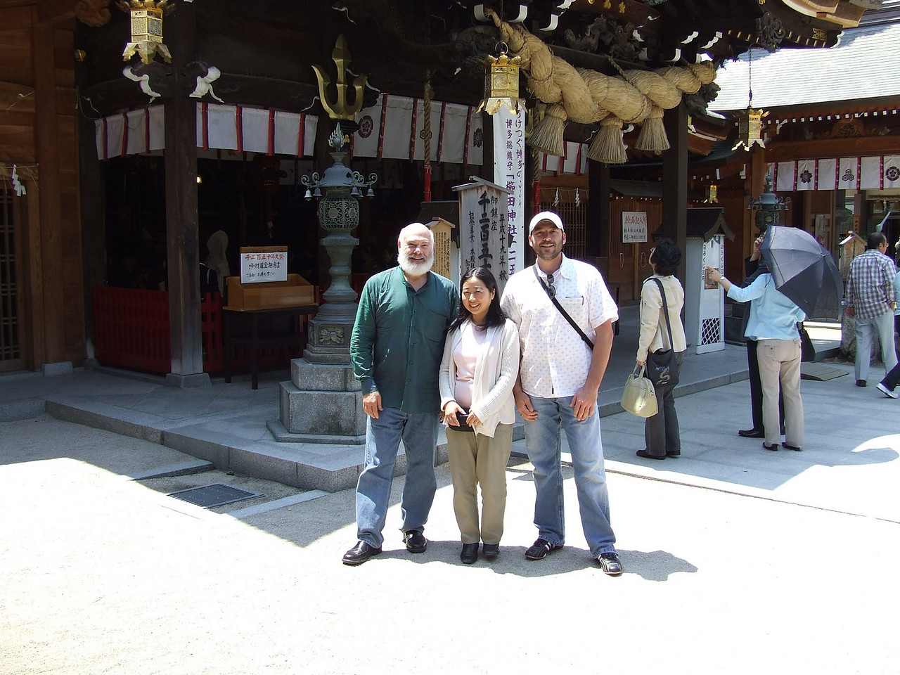 "Kushida Shrine. My wonderful interpreter Yoshiko, my friend Andre Fasciola, and me. We're standing in front of the Kushida Shrine in the heart of  old Hakata, a ward of Fukuoka City. <br /> <br /> In mid-July the shrine hosts the ""Oiyama"" event of the Yamakasa-gion festival. Hundreds of men clad only in loincloths carry heavy wooden shrines through the streets over a set route, each trying to achieve the fastest time."