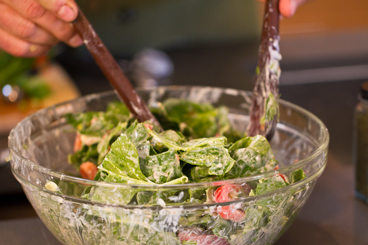 Tossing the salad to coat the spinach, tomatoes and scallions with a yogurt dressing.