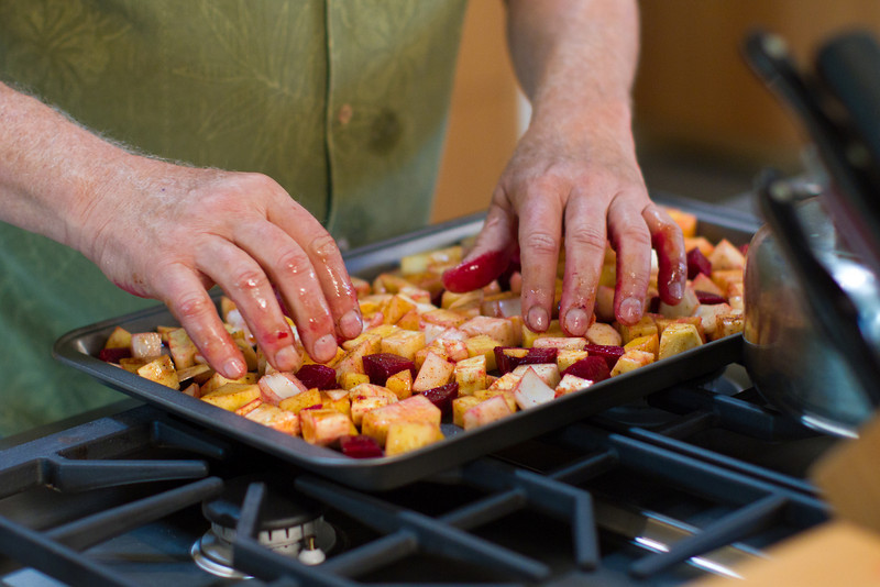 Spreading out the root vegetables in the pan for even roasting.