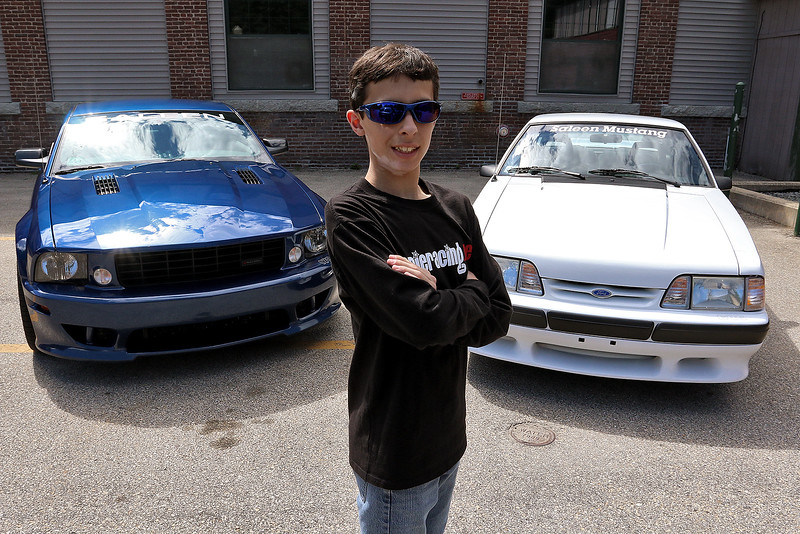Alex Lambert,16, from Dracut, who likes to be called Slimey, organized a fundraiser to benefit the Dracut Food Pantry. He is putting on a car show due to his love of cars on July 8, 2017 in the parking lot at the food pantry. Behind him are two cars the his family owns that will be at the show. The one on the left is a custom Saleen2006 S281 Super Charged Mustang and on the right is a Custom 1988 Saleen Mustang. SUN/JOHN LOVE