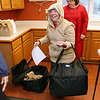 Volunteer Camille DellaPiana gets ready to deliver her Meals on Wheels to people in Dracut on Monday morning. Right behind her is STate Rep. Colleen Garry. SUN/JOHN LOVE