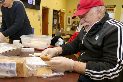 Volunteer Kevin Moreau gets some slices of bread ready to go out with the Meals on Wheels program at the Dracut Council on Aging on Monday morning. SUN/JOHN LOVE