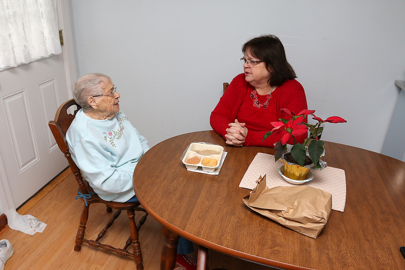 "State Rep. Colleen Garry chats with Doris Chalifoux, 88, after delivering her her ""Meals on Wheels"" meal on Monday at home in Dracut.  SUN/JOHN LOVE"