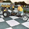 Norb Locke works the throttle on his small block Chevy 1960 top fuel dragster while 15 year old Jason Pratt works the fuel and ignition switches from the inside.